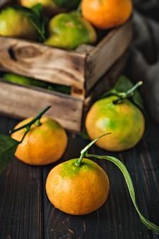 Mandarinen mit blättern auf einem altmodischen landtisch