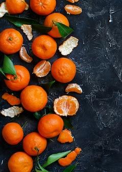Mandarinen mit blättern auf einem dunklen hintergrund