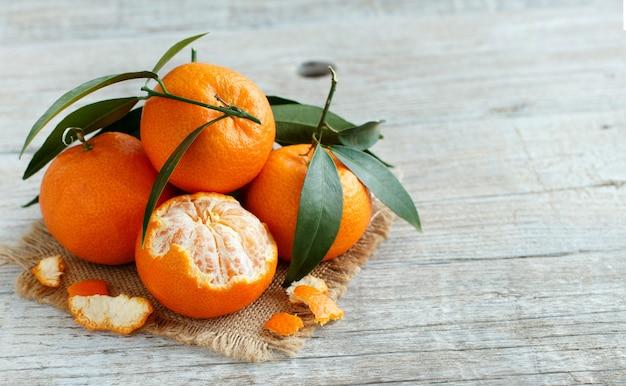 Mandarinen mit blättern auf einem holztisch schließen oben