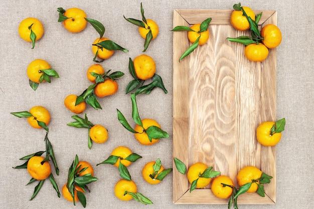 Mandarinen mit blättern auf rustikalem hintergrund