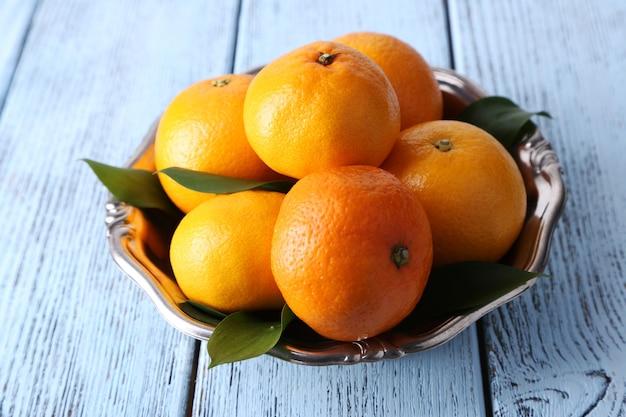 Mandarinen mit blättern auf teller auf holztisch