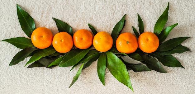Mandarinen mit blättern auf weißem plaid