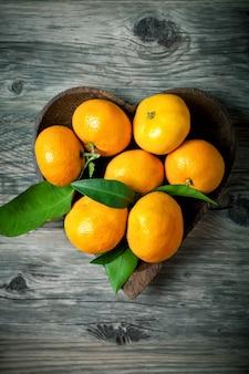 Mandarinen mit blättern im korb auf rustikalem holzhintergrund