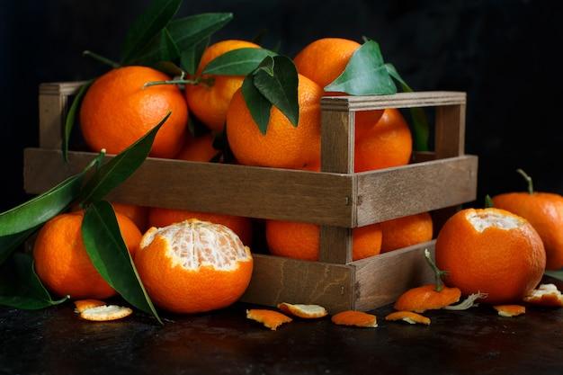 Mandarinen mit blättern in einer box auf einem dunklen hintergrund