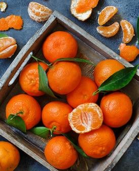 Mandarinen mit blättern in einer box auf grauem hintergrund