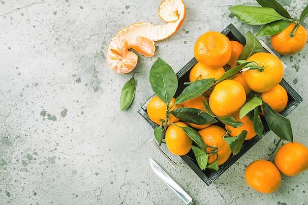 Mandarinen mit blättern in einer box über grauer putzoberfläche. draufsicht.