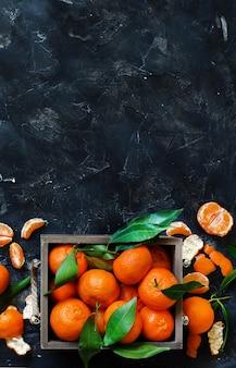 Mandarinen mit blättern in einer schachtel auf dunklem hintergrund