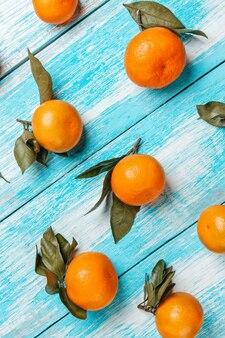 Mandarinen mit blättern liegen auf einem blauen holztisch.