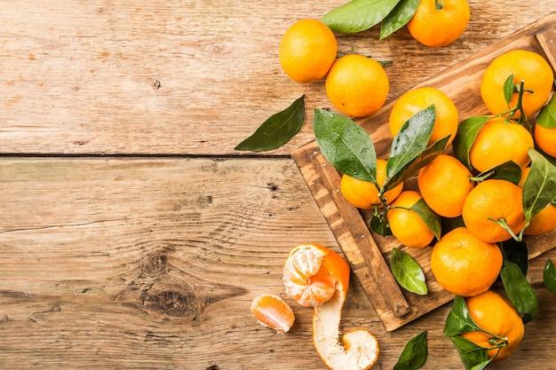 Mandarinen mit blättern über altem holz. draufsicht.