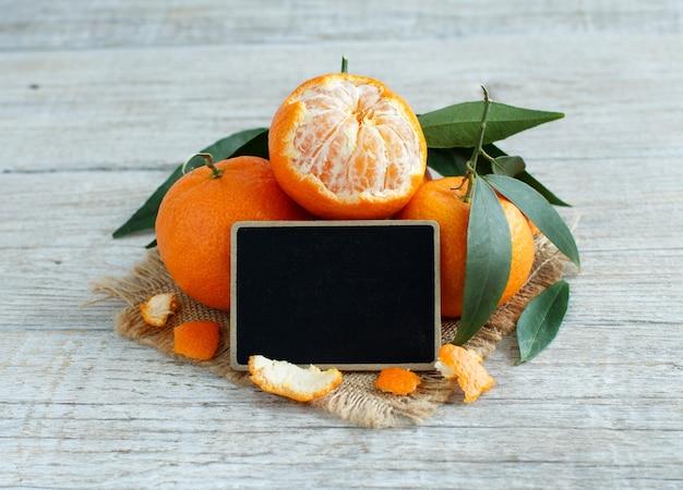 Mandarinen mit blättern und kleiner tafel auf einem holztisch