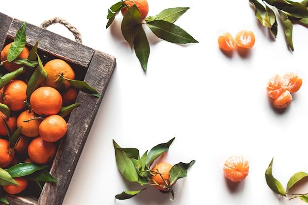 Mandarinen mit frischen blättern in holzkiste isoliert auf weiß, isoliert auf weiß, ansicht von oben