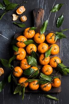 Mandarinen mit grünen blättern auf holzbrett auf dunkel