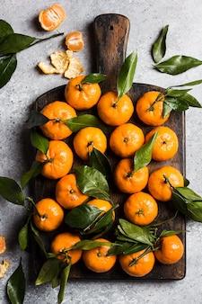 Mandarinen mit grünen blättern auf holzbrett auf licht