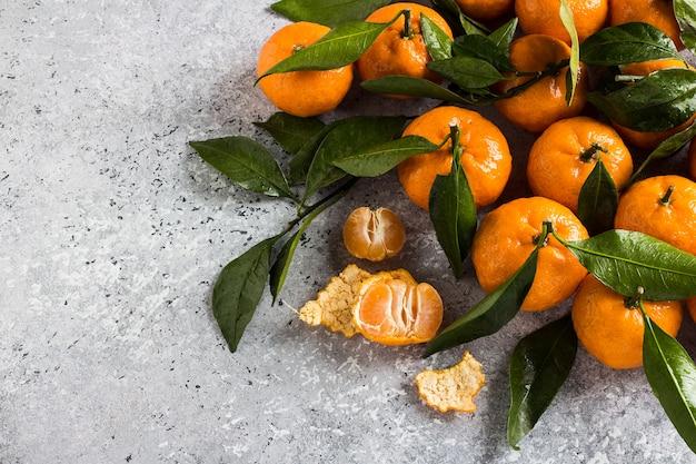 Mandarinen mit grünen blättern schließen oben auf licht