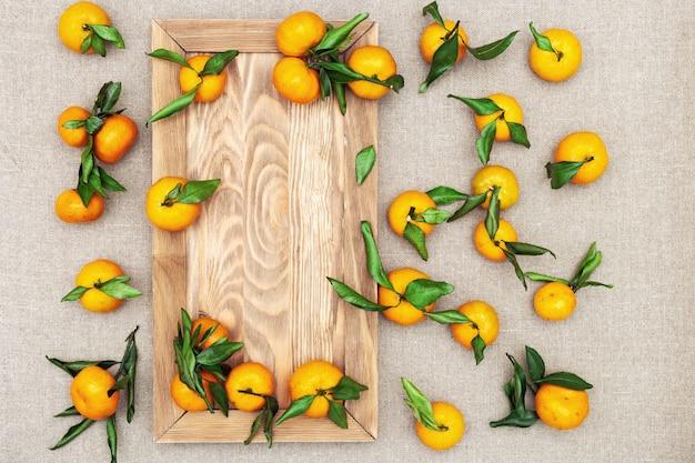 Mandarinen mit holzbrett auf sackleinen