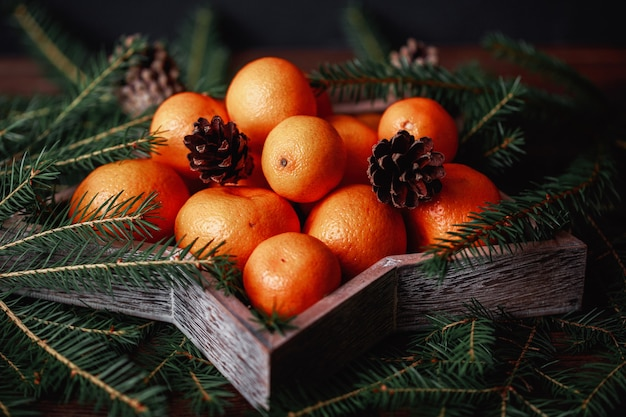 Mandarinen mit weihnachtsdekoration auf rustikaler holzkiste