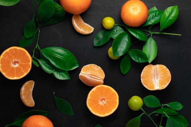 Mandarinen oder clementinen mit blättern auf einem schwarzen tisch. draufsicht
