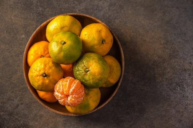 Mandarinen oder mandarinen in der bambusschale auf hölzernem hintergrund draufsicht
