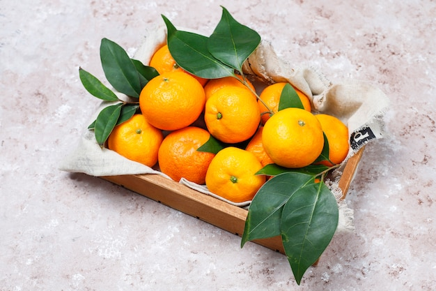Mandarinen (orangen, klementinen, zitrusfrüchte) mit grünen blättern auf betonoberfläche mit kopienraum