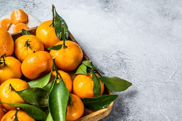 Mandarinen (orangen, mandarinen, clementinen, zitrusfrüchte) mit blättern in der hölzernen schüssel. grauer hintergrund. ansicht von oben. platz für text