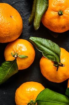 Mandarinen (orangen, mandarinen, clementinen, zitrusfrüchte) mit blättern. schwarzer hintergrund. ansicht von oben