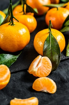 Mandarinen (orangen, mandarinen, clementinen, zitrusfrüchte) mit blättern. schwarzer hintergrund. draufsicht
