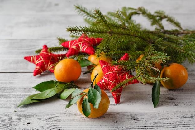 Mandarinen, tannenbrunchs, tannenzapfen und nüsse. weihnachtsessen dekorationen. sitzordnung bei tisch.