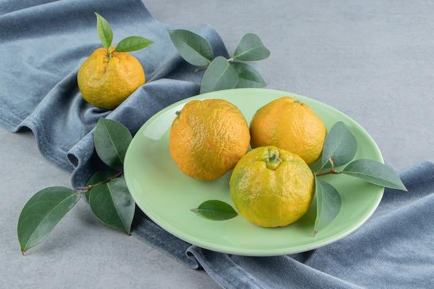 Mandarinen und blätter auf einem stück stoff auf marmor.