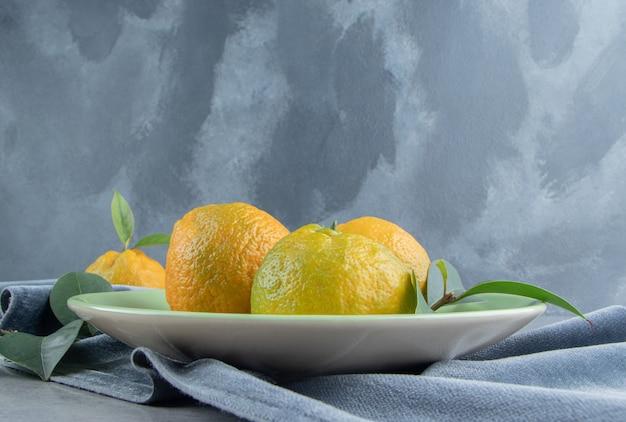 Mandarinen und blätter auf einer platte auf marmor.