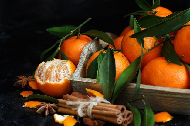 Mandarinen und gewürze auf einem dunklen hintergrund schließen