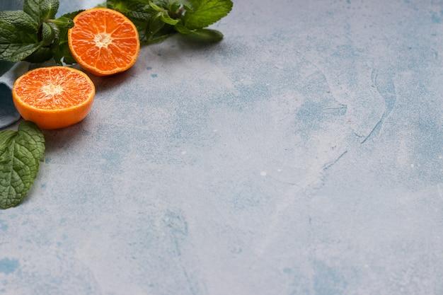 Mandarinen und minze auf einem himmelblauen stein