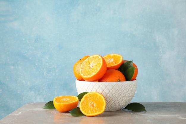 Mandarinen und schüssel auf grauem tisch vor blauem hintergrund, platz für text