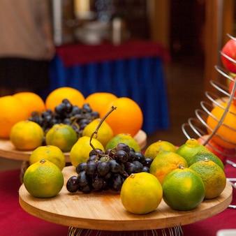 Mandarinen und trauben in einer küche auf einer holzplattform. seitenansicht.