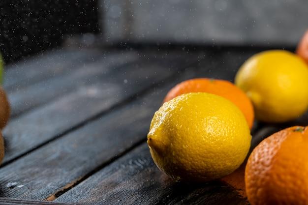 Mandarinen und zitronen auf einem holztisch