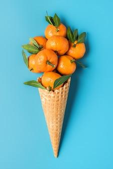 Mandarinenfrüchte in der waffeleiswaffel auf blauem hintergrund. winter weihnachtsessen konzept. vertikale ausrichtung. draufsicht. flach liegen