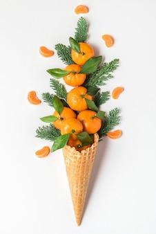 Mandarinenfrüchte in waffeleiswaffel mit tannenzweigen auf weißem hintergrund. winter weihnachtsessen konzept. vertikale ausrichtung. draufsicht. flach liegen