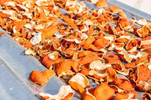Mandarinenschale auf metallfliesen, die in der sonne trocknen. nahaufnahme stockfoto.