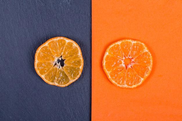 Mandarinenscheiben liegen auf orangefarbener serviette und auf schwarzem schiefer