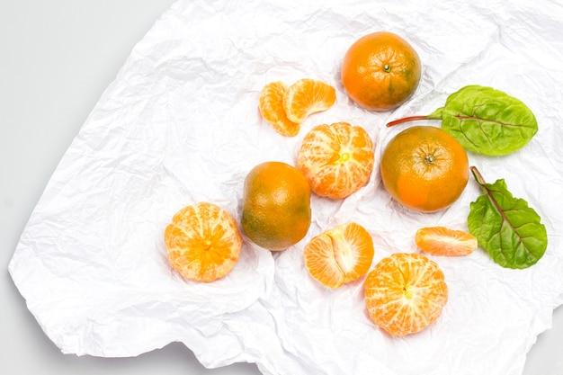 Mandarinenschnitze und eine ganze mandarine, mangoldblätter auf weißem papier. weißer hintergrund. flach liegen. speicherplatz kopieren