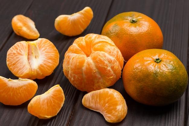 Mandarinenschnitze und ganze mandarine hautnah. holzhintergrund