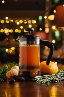 Mandarinentee in der französischen presse auf dem tisch im restaurant. heißes getränk für winter und herbst.