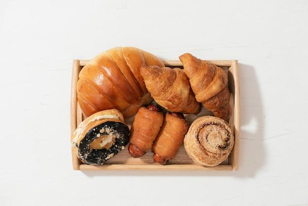 Mandel-donut-brötchen, croissant, krabbenkuchen, weicher rollkuchen mit wurst auf holzplatte, selektiver fokus