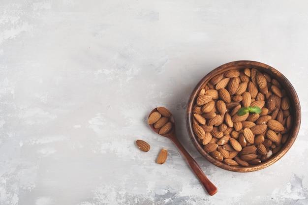Mandel in einer hölzernen schüssel, draufsicht, kopienraum, nahrungsmittelhintergrund. gesundes vegetarisches lebensmittelkonzept.
