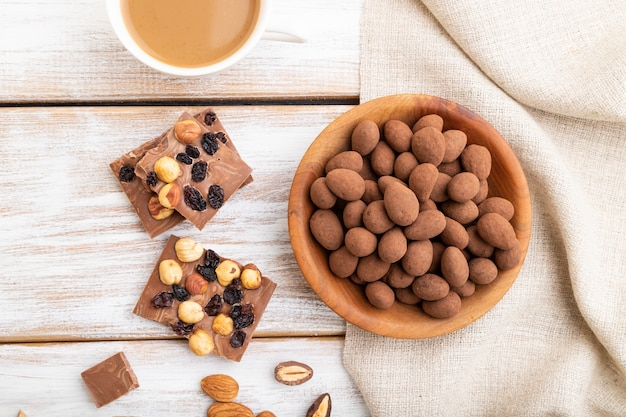 Mandel in schokoladendragees in holzteller und eine tasse kaffee auf weißem hölzernem hintergrund und leinentextil. draufsicht, nahaufnahme, flach liegen.