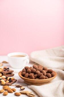 Mandel in schokoladendragees in holzteller und eine tasse kaffee auf weißer und rosa oberfläche und leinentextil