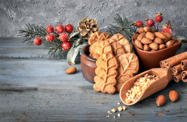 Mandelblattplätzchen, zutaten und saisonale dekorationen auf rustikalem holz, raum