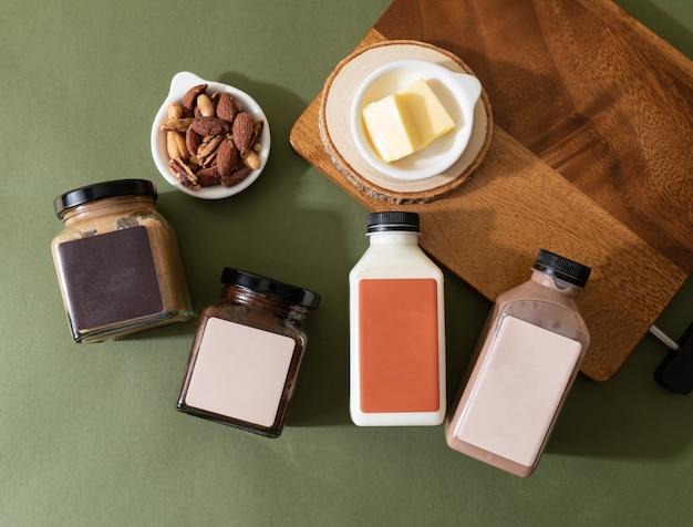 Mandelbutteraufstrich und mandelschokoladenbutteraufstrichglas mit mandelmilch und mandelschokoladenmilchflasche auf dem tisch