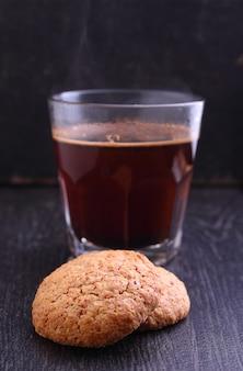 Mandelgebäck auf einem schwarzen hintergrund mit einem tasse kaffee