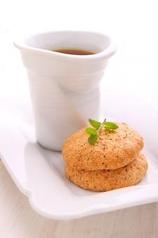 Mandelgebäck in einer weißen platte mit einer tasse tee