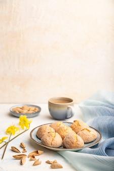 Mandelkekse und eine tasse kaffee auf einem weißen betontisch und einem blauen leinentextil. seitenansicht, kopierraum.